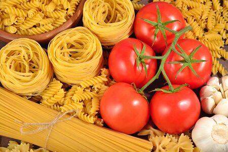 durum: Uncooked Italian pasta, ripe tomatoes branch, and garlic close up