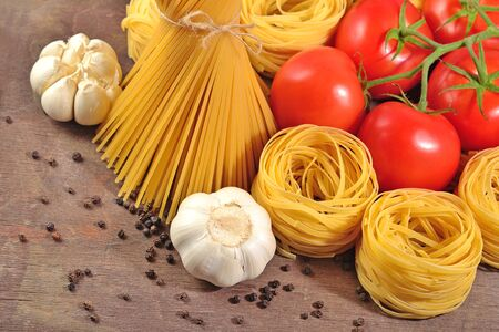 durum: Uncooked Italian pasta, ripe tomatoes branch, garlic and black pepper on a wooden background