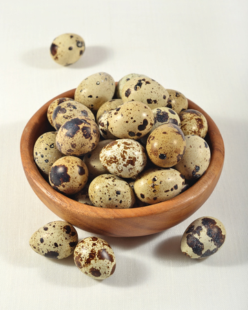 Quail eggs in a wooden bowl in a sacking background
