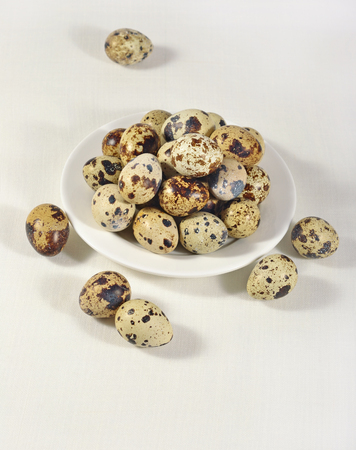 Quail eggs in a white bowl in a sacking background Zdjęcie Seryjne