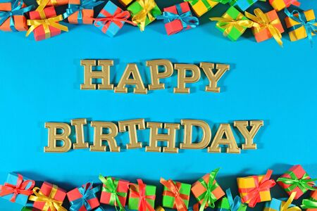 Happy birthday golden text and colorful gifts on a blue background