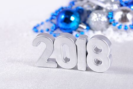 argent: 2018 year silver figures on the background of silvery and blue Christmas decorations