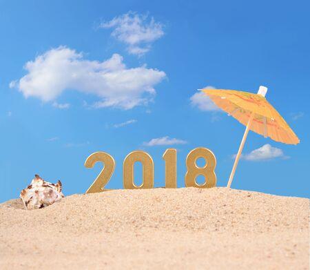 2018 jaar gouden cijfers met zeeschelp op een strandzand