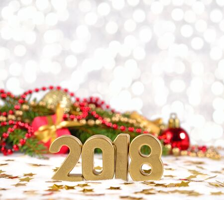 2018 year golden figures and spruce branch and Christmas decorations on a bokeh background