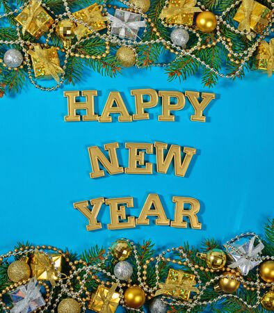 Happy New Year golden text and spruce branch and Christmas decorations on a blue background Stock Photo