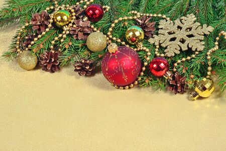 Christmas decorations and spruce branch and cones on a golden background