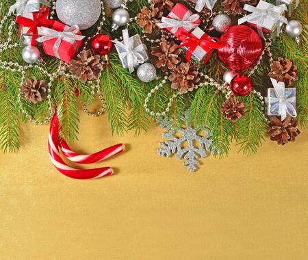 Christmas decorations on a spruce branch on a golden background