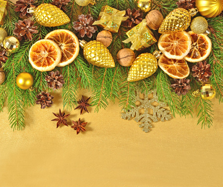 is green: Dried oranges and cones, Christmas decorations and spruse branch on a golden background