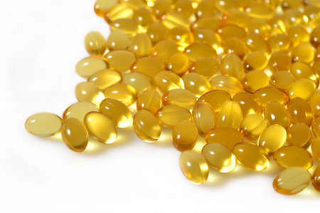 Omega-3 fish fat oil capsules close up on a white background.