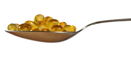 Omega-3 fish fat oil capsules in spoon on a white background Stock Photo