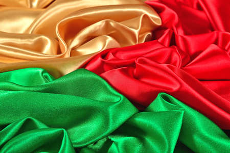 Natural golden, red and green satin fabric as background texture