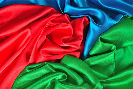 Natural blue, red and green satin fabric as background texture Imagens