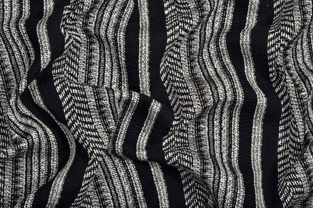 Draped black and white striped fabric as background texture Stock Photo