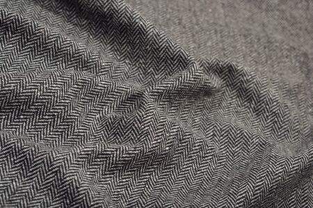 Draped herringbone tweed wool fabric as background texture Archivio Fotografico