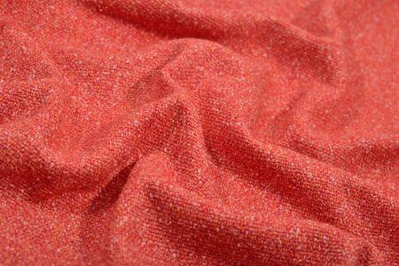 Draped orange tweed wool fabric as background texture