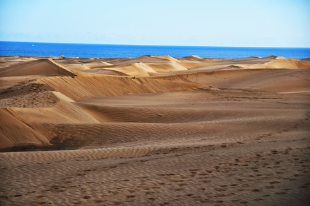 View on sunny Maspalomas dunes in Gran Canaria in daytime. Cloudy sky on background. Stock Photo