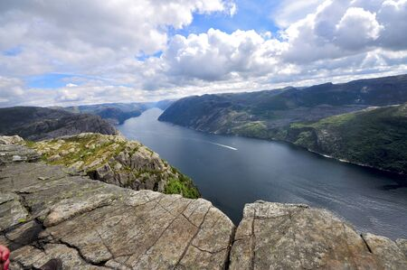 tourists in preikestolen or pulpit in Norway on a day with clouds