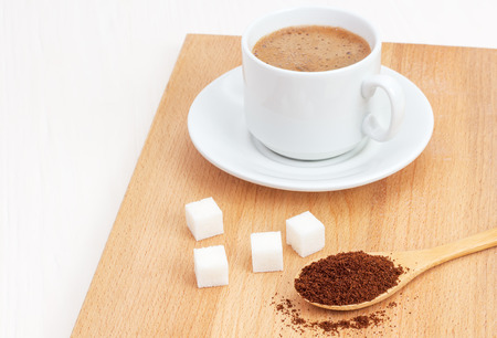 sugar, ground coffee in a wooden spoon on the table
