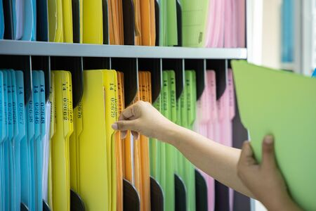 Woman working with documents in office, closeup - Search files document Banque d'images