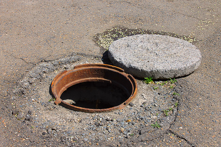 disuse: Photo on which is depicted a deep open manhole. Stock Photo