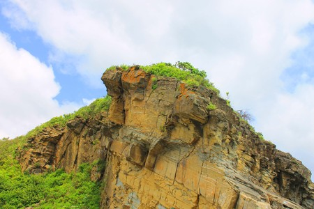The photo depicts a small rock with vegetation. Stock Photo