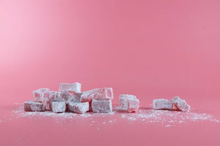 Composition of Turkish delight, lokum, on a pink background and powdered sugar spilled on the table Фото со стока
