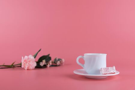 A white cup of tea with a piece of lokum, turkish delight on the side, with delicate flowers on a pink background. Afternoon tea concept