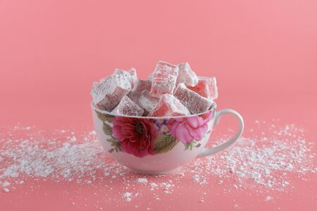 A white mug with painted flowers full of lokum, a turkish delight, on a pink background and powdered sugar spilled on the table