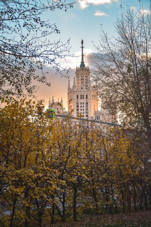 View of the Stalinist skyscraper through the autumn trees at sunset