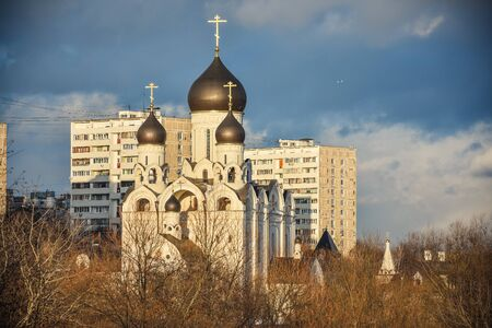 White Church with black domes at sunset, the church on the background of residential buildings