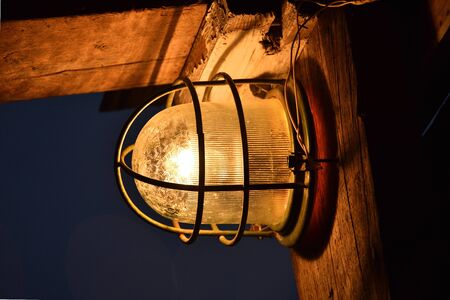 burning lantern in a metal grill, bright yellow light from the lantern
