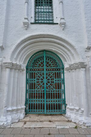 green metal door in a white building, passage to the building