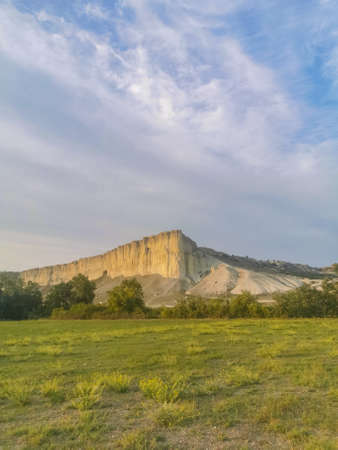 White rock in the Crimea. White rock Sights of Crimea. High rock Rocky mountain. White rock against a beautiful sunset, light clouds fly over the rock and the road leads to the foot of the rock. Banco de Imagens