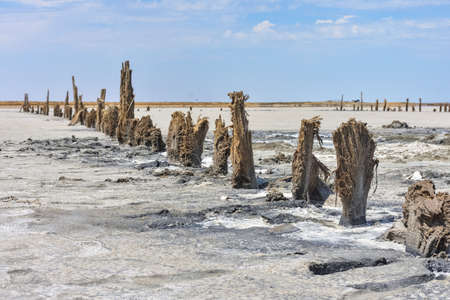 Stunning, white salt desert or salt lake. remains of a wooden building in a salt lake. dried up salt lake, salt-eaten building, rotten wooden building