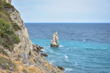 a piece of rock near the sea near the coast, a view of the coastal rocks near the castle Swallow's Nest in Crimea, a detached large piece of rock in the middle, coastline on the left, sea view