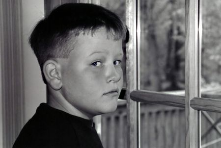 glancing: Young boy glancing back from looking out a door.