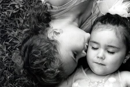 Black and white portrait of two sisters, the older kissing the younger.