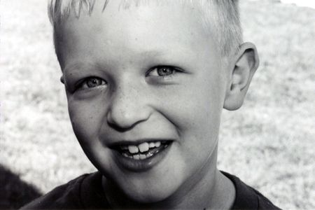 Horizontal black and white portrait of a young boy.