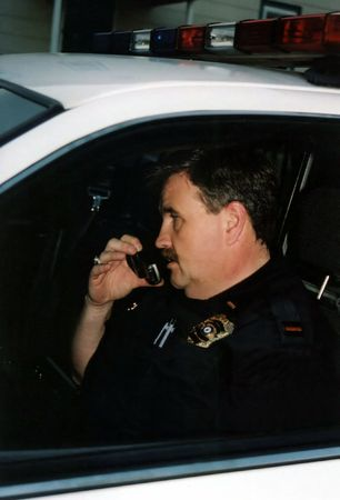 rely: Police officer in car talking on telephone. Stock Photo