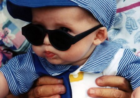 disapprove: Baby peeking behind glasses, being held by grandmother.