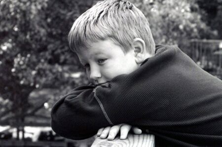 Black and white portrait of a pensive boy.