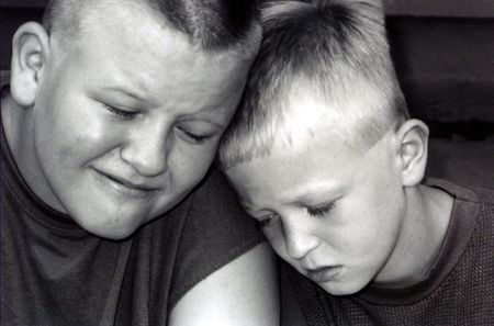torment: Black and white portrait of two sad boys.