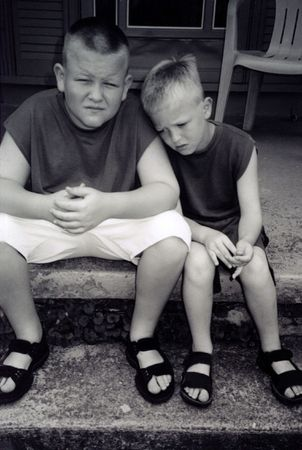 Black and white of two unhappy boys on a doorstep.