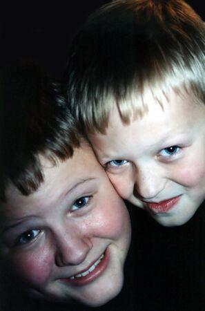 Portrait of two brothers cheek to cheek. Фото со стока