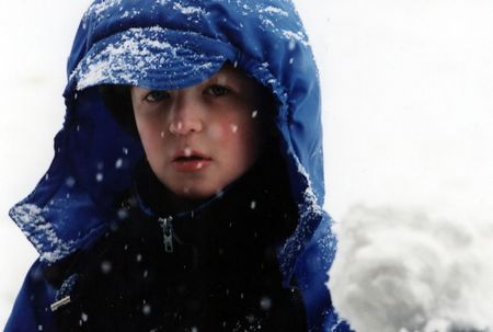 Boy in a snowstorm, holding a snowball.