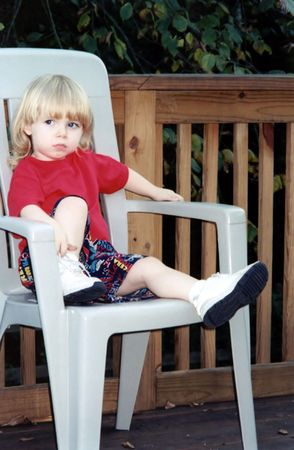 Unhappy toddler sitting on a chair.