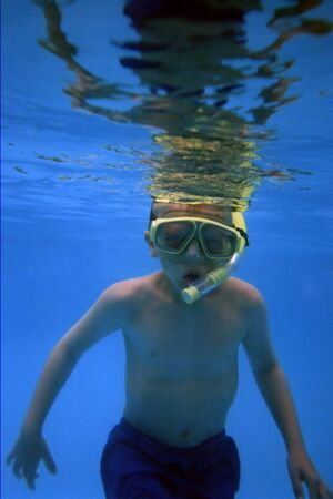 Boy under water using snorkel.