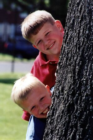 clowning: Two brothers peeking out from behind a tree.