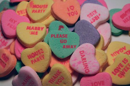Candy heart messages with Please Go Away on center heart.