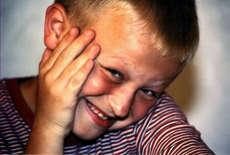 coy: Portrait of boy with coy expression, hand to cheek.